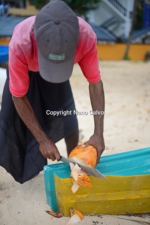 Coconut seller cuts the coconut on Unawatuna beach, Sri Lanka