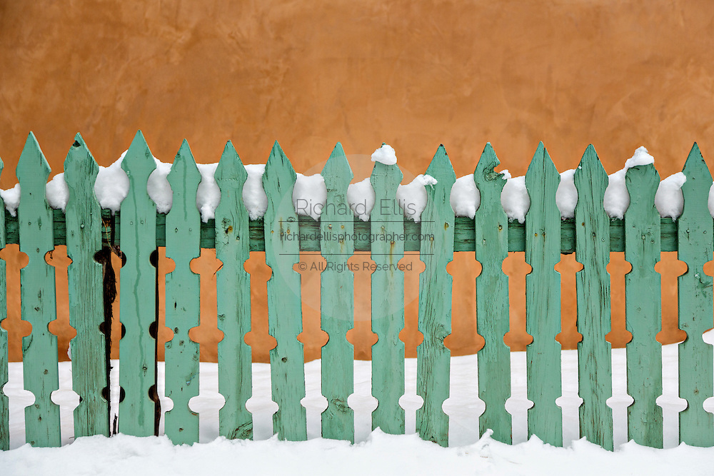 Turquoise picket fence covered in snow against an adobe wall along Canyon Road in Santa Fe, New Mexico.