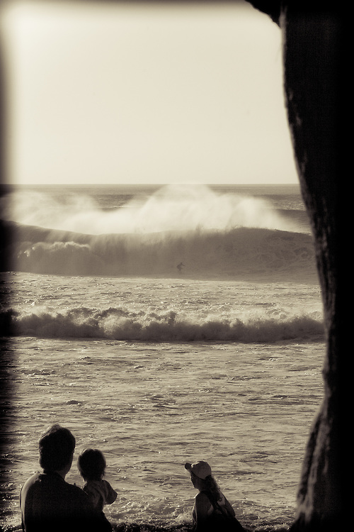 A family watches a surfer at Banzai Pipeline from Ehukai Beach Park, Oahu, Hawaii, USA.