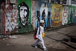 A Boy in his school best walks out of a crowded neighbourhood in North jakarta, Indonesia.