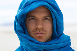 face of a man with blue eyes wrapped in blue fabric