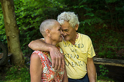 """Charlie Branham, a former coal miner, poses with his wife Donna outside their home in Lenore, West Virginia. Donna Branham shaved her head on the steps of the West Virginia Capitol with a group of women in protest to mountaintop-removal mining. The shaving of their heads was symbolic of the mountains that have been stripped of all of the living things on them. It was also symbolic of the many people who are sick or dying as the result of Mountaintop Removal. Mountaintop Removal is a method of surface mining that literally removes the tops of mountains to get to the coal seams beneath. It is the most profitable mining technique available because it is performed quickly, cheaply and comes with hefty economic benefits for the mining companies, most of which are located out of state. It is the most profitable mining technique available because it is performed quickly, cheaply and comes with hefty economic benefits for the mining companies, most of which are located out of state. Many argue that they have brought wage-paying jobs and modern amenities to Appalachia, but others say they have only demolished an estimated 1.4 million acres of forested hills, buried an estimated 2,000 miles of streams, poisoned drinking water, and wiped whole towns from the map. """"People don't know how hard it is on the Appalachian people,"""" Branham said of mountaintop-removal mining. """"They have no idea. And they don't want to know. As long as they don't have to look at it, they can ignore it."""" © Ami Vitale"""