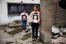 Zhao Xiao Qiong, 36, holding a picture of  daughter Lan Xiao Juan, 10, right, and Yang Zai Yin, holding a picture of  son Liu Chao, 12, are seen  at Fuxin No.2 Primary  School in Wufu, Sichuan province May 24, 2008. Both mothers have only one child.