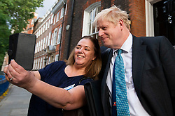 © Licensed to London News Pictures. 18/07/2019. London, UK. Conservative Party leadership contender Boris Johnson takes a selfie with a member of the public as he leaves an address in Westminster. He is one of two remaining candidates in the leadership contest .  Photo credit: George Cracknell Wright/LNP