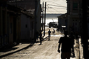 People are silhouetted as they walk on the streets of Baracoa, Cuba, early on the morning of Sunday July 13, 2008.