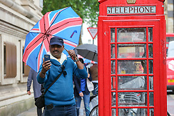 © Licensed to London News Pictures. 10/06/2019. London, UK. A tourist shelters from the rain beneath Union Jack  umbrella takes a selfie with the red telephone box as rain falls in the capital. The Met Office has just issued an amber warning for more rain, covering London and parts of southeast England later today Photo credit: Dinendra Haria/LNP