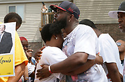 Michael Brown Sr., at the spot where his son was killed, comforts his wife Cal Brown during 4 1/2 minutes of silence to mark the one year anniversary of the killing of son Michael Brown Jr. in Ferguson, Missouri August 9, 2015.  Several hundred people gathered in Ferguson, Missouri, on Sunday to mark the one-year anniversary of the shooting death of an unarmed black teenager by a white police officer that sparked protests and a national debate on race and justice.  REUTERS/Rick Wilking