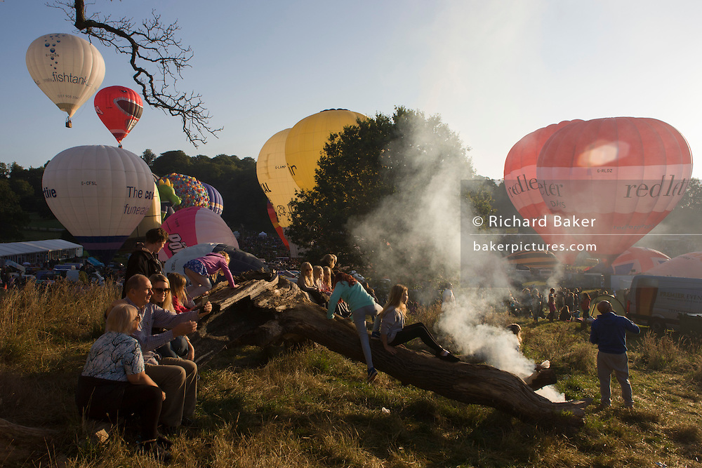 Families watch the mass lift-off by balloons at Bristols annual fiesta at Ashton Court, UK.