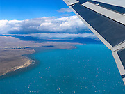 "A jet departing El Calafate International Airport (code FTE, 20 km east of town) flies over Lake Argentina in the southern Andes mountains, north towards Buenos Aires, Argentina, South America. Glaciers grind rock finely into glacial flour which flows suspended in water into the lake and creates a bright turquoise color. El Calafate is named from a little bush with yellow flowers and dark blue berries that is very common in Patagonia: the calafate (Berberis buxifolia), Spanish for ""caulk"". El Calafate is an important tourist hub for Los Glaciares National Park, including Perito Moreno Glacier. The foot of South America is known as Patagonia, a name derived from coastal giants, Patagão or Patagoni, who were reported by Magellan's 1520s voyage circumnavigating the world and were actually native Tehuelche people who averaged 25 cm (or 10 inches) taller than the Spaniards."