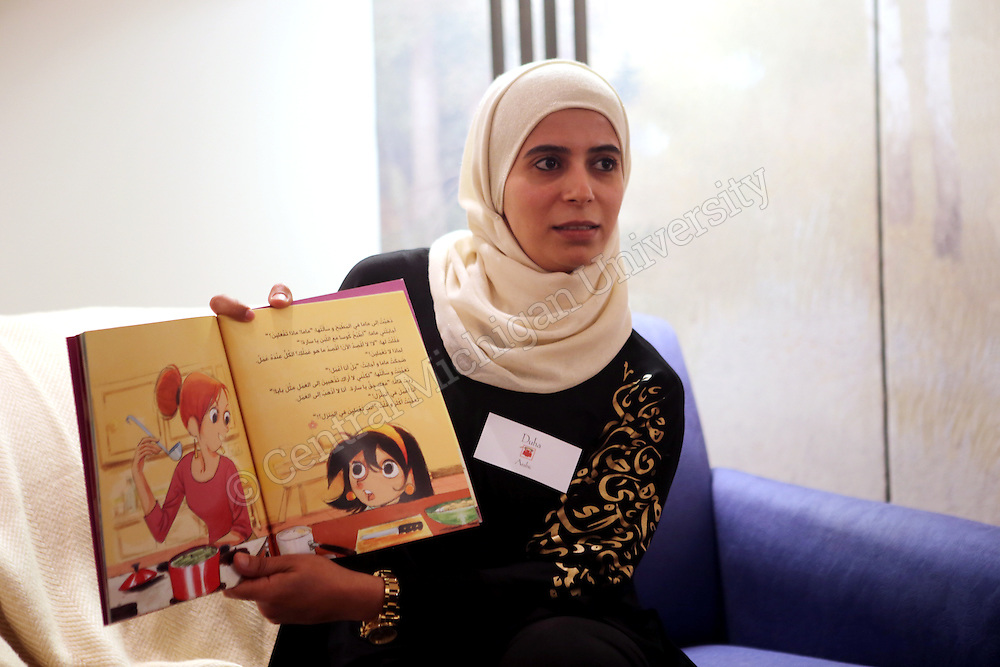 Graduate student Duha Hamed reads a children's book in Arabic to Grandparents U participants photo by Emily Mesner