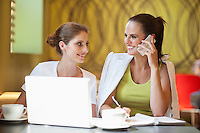 Young woman sitting with friend using cell phone at cafe