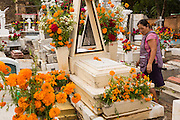 A woman cleans and decorates the gravesite of a relative at Xoxocatian cemetery decorated with flowers and candles for the Day of the Dead Festival known in spanish as Día de Muertos on October 31, 2014 in Oaxaca, Mexico.