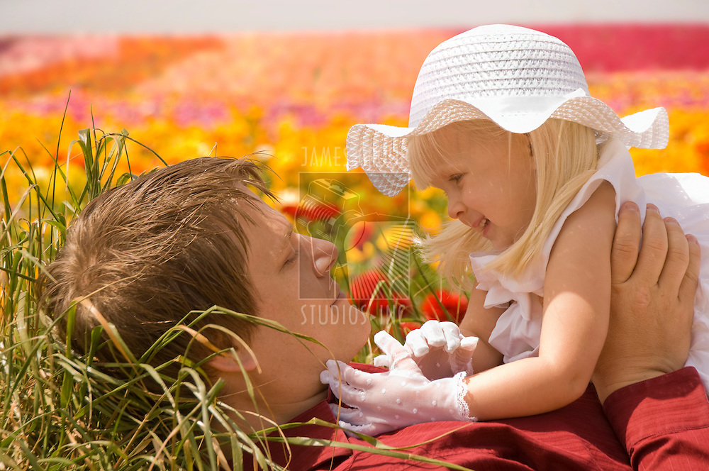 Father and young daughter lying in a field of flowers