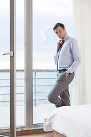 Portrait of worried businessman adjusting necktie by glass door in hotel