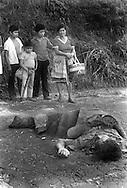 Pobladores de San Ramon en San Salvador observan los restos de un trabajador que fue asesinados por miembros de los escuadrones de la muerte 1989.(IL Photo).