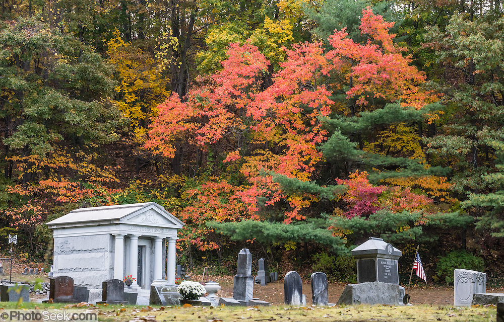 In Watkins Glen, fall foliage bursts in color over St Marys Cemetery along the Indian Trail in mid October. In Watkins Glen, the spellbinding Gorge Trail winds two miles over and under 19 waterfalls of Glen Creek, which descends 400 feet under 200-foot-high cliffs. Watkins Glen State Park is south of Seneca Lake in Schuyler County in the Finger Lakes region New York, USA. The Devonian sedimentary rocks are mostly soft shales, with some layers of harder sandstone and limestone.