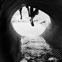 Friends sitting on an outflow pipe