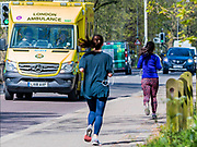 Joggers pass an ambulance on the south circular - Clapham Common is pretty quiet. The 'lockdown' continues for the Coronavirus (Covid 19) outbreak in London.