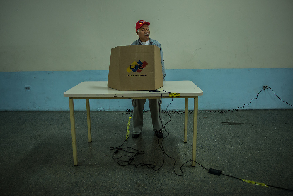 """CARACAS, VENEZUELA - JULY 16, 2017: A few dozen government supporters participated in a rival vote, held right next to a plaza filled with thousands of people in line to vote in the """"Popular Consultation"""" symbolic vote called for by the opposition. Maduro loyalists held a """"drill"""" for the constituent assembly election, and the voting exercise was covered widely on state-run news outlets. The government prohibited TV and Radio stations to air coverage of the opposition's vote.  The government requires government employees to vote or risk being fired. They are also criticized for insinuating that people who benefit from government programs will lose their benefits if they do not vote for the ruling Socialist party. Many people say they continue to vote for them, out of fear.  PHOTO: Meridith Kohut"""