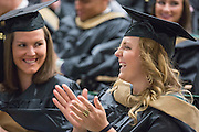 Valerie Dunlap, left, and Aspen Echelmeier, right, laugh at the Ohio University College of Business Commencement Ceremony on April 9, 2016. (Photo by Emily Matthews)