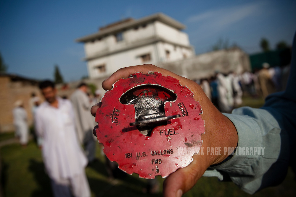 A local man displays a fuel cap believed to come from the US helicopter that was reportedly shot down outside the compound where Osama Bin Laden was killed in an operation by US Navy Seals, on May 3, 2011, in Abottabad, Pakistan.  The operation, code-named Operation Neptune Spear, was launched from neighbouring Afghanistan by Seal Team Six. U.S. forces took bin Laden's body to Afghanistan for identification, then dumped it the Arabian Sea. Pakistan has since been widely suspected as having prior knowledge of his whereabouts as the compound was less than a kilometre from the country's biggest military academy. Osama bin Laden was allegedly responsible for supporting the bombing of the US Embassy in Nairobi, Kenya, the attack on the USS Cole and the suicidal attacks of September 11, 2001 in the US. (Photo by Warrick Page)