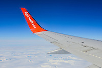The orange Air North 737-500 winglet contrasting with the blue sky.