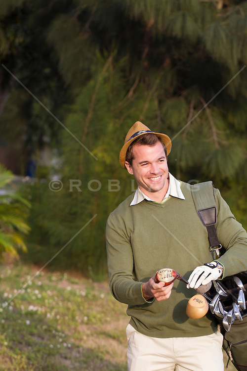 weekend golfer holding a golf club and ball outdoors