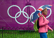 © Licensed to London News Pictures. 18/07/2012. London, UK People with umbrellas walk past an Olympic symbol. Rain in Central London today 18th July. Photo credit : Stephen Simpson/LNP