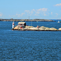 G&auml;vesk&auml;r Light in Archipelago in Gothenburg, Sweden <br /> Gothenburg&rsquo;s coastline is formed by the Kattegat Sea and the Skagerrak Strait, both of which empty into the Baltic.  Here you will discover a string of islands called G&ouml;teborg Sk&auml;rg&aring;rd. The Northern Gothenburg Archipelago has ten islands that can be reached by bridge or ferry. The Southern Archipelago is car free and is dotted with over ten thousand homes, most of which are used only during the summer. Many are clustered into small communities but my favorites are the tiny cabins that are suspended along the rocky shore.  I also enjoyed seeing all of the lighthouses.  This 33 foot concrete tower with a red keeper&rsquo;s house is the G&auml;vesk&auml;r Light. It was built in 1964 yet the station has been perched on this tiny islet since 1886.