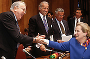 Secretary of State Madeleine Albright shakes hands with Senate Foreign Relations Committee Chairman Senator Jesse Helms, as Senator Joseph Biden looks on before a hearing on chemical weapons April 8, 1997. The Senate faces a vote to ratify the global chemical weapons treaty.