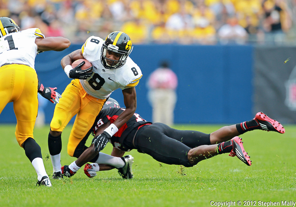 September 01 2012: Iowa Hawkeyes wide receiver Don Shumpert (8) tries to avoid a diving tackle by Northern Illinois Huskies defensive back Jimmie Ward (15) during the first half of the NCAA football game between the Iowa Hawkeyes and the Northern Illinois Huskies at Soldiers Field in Chicago, Illinois on Saturday September 1, 2012. Iowa defeated Northern Illinois 18-17.