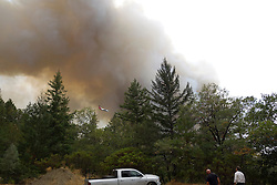 September 12, 2015 - Lake County, California. Cal Fire aircraft fighting fire near Hoberg's Resort as local residents look on.