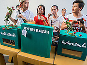 "14 FEBRUARY 2015 - BANGKOK, THAILAND:  Pro-democracy protestors stand behind a mock ballot box in Bangkok. Dozens of people gathered in front of the Bangkok Art and Culture Centre in Bangkok Saturday to hand out red roses and copies of George Orwell's ""1984."" Protestors said they didn't support either Red Shirts or Yellow Shirts but wanted a return of democracy in Thailand. The protest was the largest protest since June 2014, against the military government of General Prayuth Chan-Ocha, who staged the coup against the elected government. Police made several arrests Saturday afternoon but the protest was not violent.     PHOTO BY JACK KURTZ"