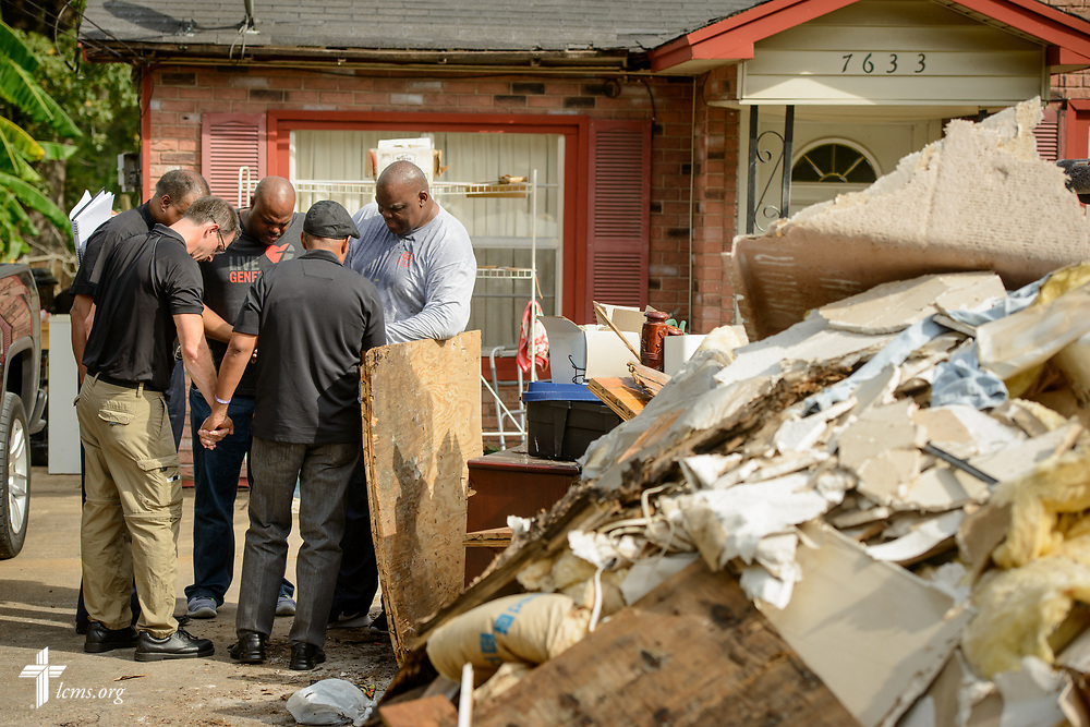 LCMS leaders and a local pastor pray with the son of Hurricane Harvey victims outside his parent's house on Tuesday, Sept. 26, 2017, in Houston. LCMS Communications/Erik M. Lunsford