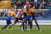 Krystian Pearce of Mansfield Town (5) and Hayden White of Mansfield Town (2) are held by Dean Moxey of Exeter City (21) during the EFL Sky Bet League 2 match between Mansfield Town and Exeter City at the One Call Stadium, Mansfield, England on 15 September 2018.