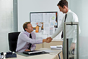 Two businessman shaking hands at office