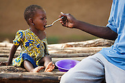 A man feeds his child in the village of Yezegu, Ghana on Friday November 12, 2010.