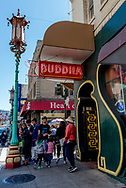 Entrance to the Buddha Lounge in San Francisco Chinatown, Grant Ave. An ornamental Chinese street lamp, one of several in Chinatown, stands outside as people walk by. Street scene.