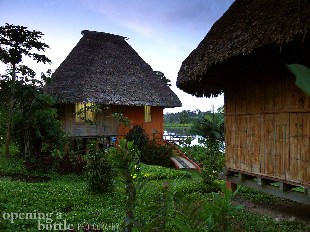 Two thatch-roofed cabanas at the Napo Wildlife Center, a Quechua-run ecolodge in the Amazon of Ecuador.