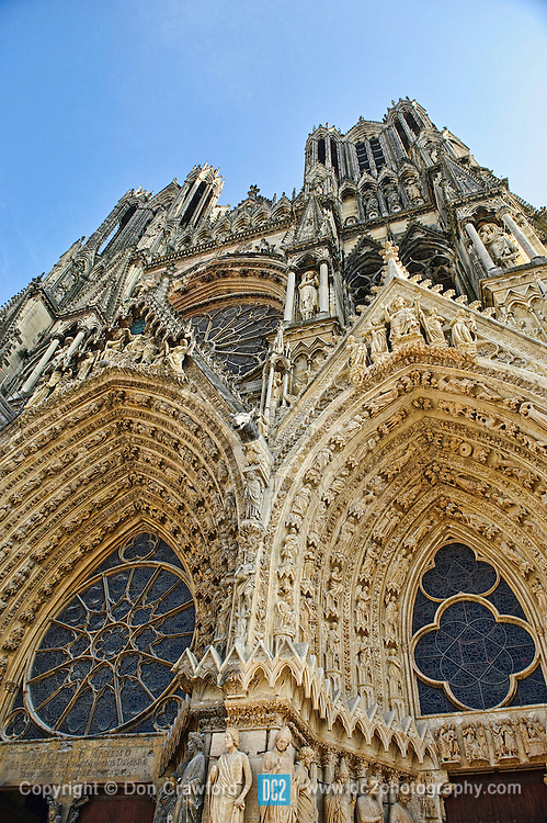 Detail of front fascade showing beautiful ornate sculptures and carvings...Notre-Dame de Reims (Our Lady of Rheims) is the Roman Catholic cathedral of Reims France...Notre-Dame de Reims cathedral, the former Abbey of Saint-Remi, and the Palace of Tau were added to the list of UNESCO World Heritage Sites in 1991.