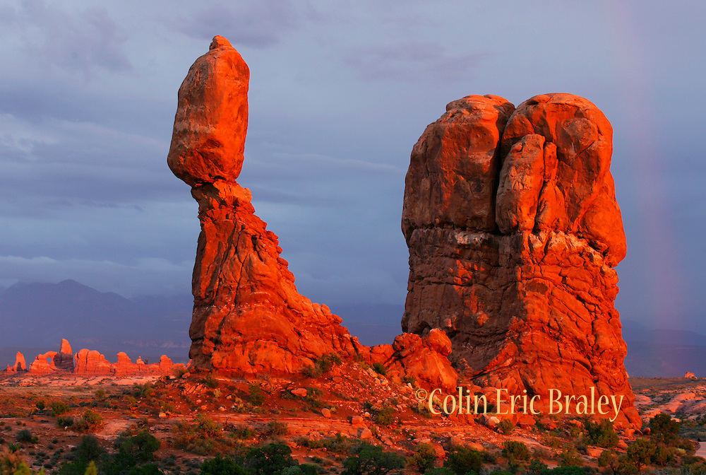A passing storm and the last moments of a sunset bring out the red hues of Arches National Park as the rock formation known as Balanced Rock glows. Colin Braley/Wild West Stock