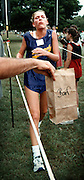 "As she crosses the finish line is discomfort, a cross-country racer eyes the ""barf bag"" awaiting her being held by her father. She throws up after almost every race so they have learned to keep a bag handy."
