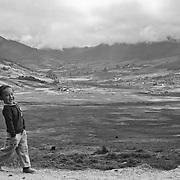 A Bhutanese little boy walking through the Phobjikha Valley, Gangtey, Bhutan, Asia