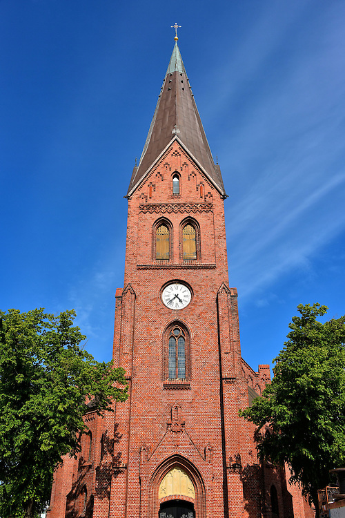 Warnem&uuml;nde Church Clock Tower in Warnem&uuml;nde, Germany<br /> The first Warnem&uuml;nde Church was built in the mid-13th century about fifty years after this town on Germany&rsquo;s northern coast was founded. When this brick, Evangelical Lutheran church was consecrated in 1871, the prior building was demolished.  Fortunately, some its beautiful interior was saved and incorporated into this new Gothic Revival structure.  Examples include a 15th century altar and a 16th century pulpit.  Especially unique are two votive ships that are suspended from the ceiling. They were gifts by local mariners.