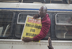 November 18, 2017 - Harare, Zimbabwe - Protesters demanding President Robert Mugabe stand down, look up and cheer as an army helicopter flies over the crowd, as they gather in front of an army cordon on the road leading to State House in Harare, Zimbabwe Saturday, Nov. 18, 2017. In a euphoric gathering that just days ago would have drawn a police crackdown, crowds marched through Zimbabwe's capital on Saturday to demand the departure of President Robert Mugabe, one of Africa's last remaining liberation leaders, after nearly four decades in power. (Credit Image: © Belal Khaled/NurPhoto via ZUMA Press)