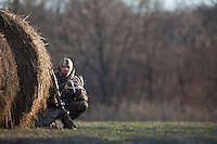 DEER HUNTER WITH A MOSSBERG SHOTGUN AND WEARING REALTREE CAMOUFLAGE HIDING BEHIND HAY BALES AND GLASSING WITH BINOCULARS