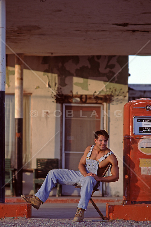 man in overalls and no shirt at an old gas station