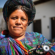 A woman shows off her woven textiles for sale on the streets of downtown Antigua Guatemala. Guatemala has a very strong traditional of weaving. Famous for its well-preserved Spanish baroque architecture as well as a number of ruins from earthquakes, Antigua Guatemala is a UNESCO World Heritage Site and former capital of Guatemala.