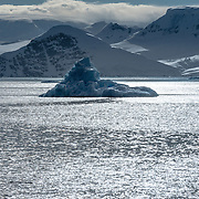 An iceberg is silhouetted against the sun catching the water in the Gerlache Strait on the western side of the Antarctic Peninsula.