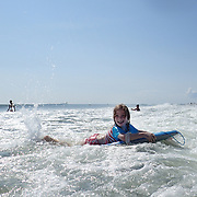 A young girl in the surf in the height of summer on Cisco Beach, Nantucket, Nantucket Island, Massachusetts, USA. Photo Tim Clayton